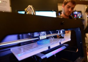 "Visitors look at a 3D printer printing an object, during ""Inside 3D Printing"" conference and exhibition in New York, April 22, 2013. The exhibition features on April 22-23, 2013, tutorials and seminars offering blueprints on how to invest and utilize 3D printing in coming years, as well as leading manufacturers and developers displaying their latest 3D printers and services. AFP PHOTO/Emmanuel Dunand        (Photo credit should read EMMANUEL DUNAND/AFP/Getty Images)"